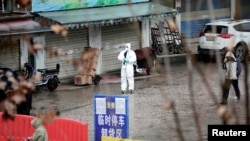 A worker in a protective suit is seen at the closed seafood market in Wuhan, Hubei province, China January 10, 2020. REUTERS/Stringer