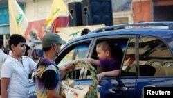 시리아 당국이 쿠사이르를 장악하자 레바논의 헤즈볼라 지지자들이 5일 시아파 마을에서 사탕을 나눠주고 있다 (자료 사진)