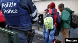 Seorang petugas polisi dalam keadaan siaga melakukan penjagaan terhadap sebuah sekolah di Brussels, Belgia (25/11).
