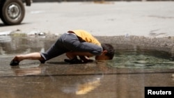 A boy is seen drinking from a puddle created by a burst water pipe in Aleppo's Karm al-Jabal district June 2, 2013.