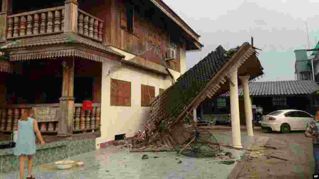 A woman looks at a damaged house following an earthquake in Chiang Rai, northern Thailand, May 5, 2014.