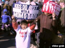 """一个男孩打出""""有爸妈的孩子做得最好""""的牌子(视频拦图)"""