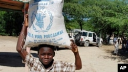 A Haitian child carries a bag of food during a food distribution from the United Nations World Food Program, Programme Alimentaire Mondial in Balan a suburb of Ganthier, (File).