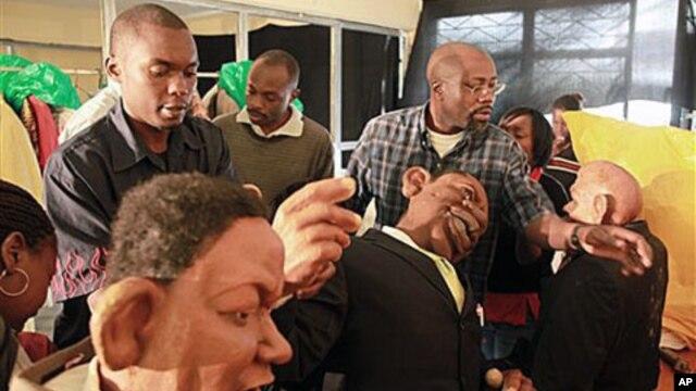 FILE - 'XYZ Show' creator Godfrey 'Gado' Mwampembwa (r) prepares the puppets for the show at his studio in Nairobi, Kenya, 21 May 2009.