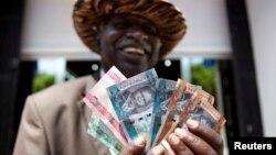 Raia wa Sudan Kusini akishikilia fedha inayotumika nchini humo.