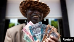 FILE - A man from South Sudan displays currency notes outside the Central Bank of South Sudan in Juba, July 18, 2011. South Sudan's central bank said it would introduce a 500-pound bill this month.