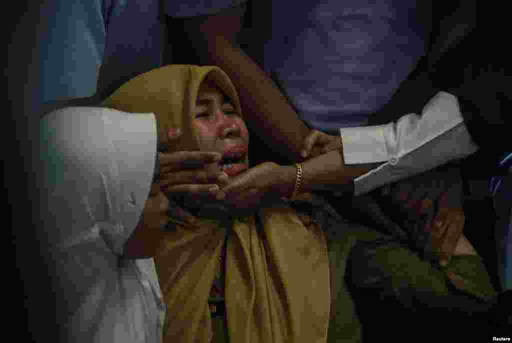 Relatives of passengers of Lion Air, flight JT610, that crashed into the sea cry at Depati Amir Airport in Pangkal Pinang, Belitung island,.