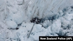 The wreckage of a helicopter carrying tourists is seen crashed in a crevasse on Fox Glacier, a scenic glacier in South Island, New Zealand, Nov. 21, 2015. All seven people, one pilot and six tourists, aboard the helicopter are believed to have been killed.
