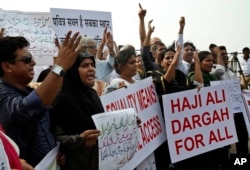 FILE - People shout slogans to support women's rights activists opposing the ban on women entering the Muslim shrine Haji Ali Dargah, in Mumbai, India, April 28, 2016.