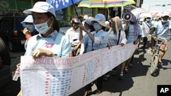 Cambodian protesters from Boueng Kak lake march with a banner displaying the thumb prints of fellow land owners who have been evicted from their homes, as they demand compensation, in Phnom Penh, Cambodia, May 4, 2012.