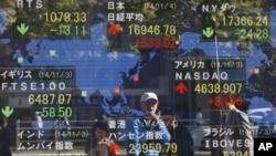 Hình người phản chiếu trên bảng điện tử chứng khoán tại Tokyo ngày 4/11/2014.