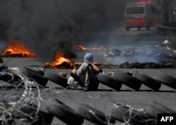 Palestinian men burn tires during a protest in the West Bank city of Ramallah, April 6, 2018.