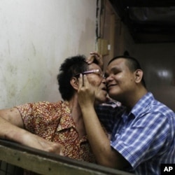 Lai Kwan, sharing a tender moment with her son, Kok Leong, who is born with severe mental disabilities. She believes it is a consequence of her working in the rare earth factory in Bukit Merah.