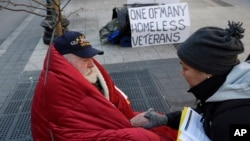 FILE - A homeless Korean War veteran speaks with an outreach coordinator on a sidewalk in Boston, Massachusetts, Nov. 20, 2013.