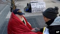 FILE - A homeless Korean War veteran speaks with an outreach coordinator on a sidewalk in Boston, Massachusetts.