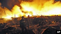 Firemen look around at the scene of an explosion at a warehouse in Rangoon, Burma, December 29, 2011.