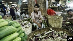 A woman sells produce at a vegetable wholesale market in Yangon (file photo – 25 Apr 2010)