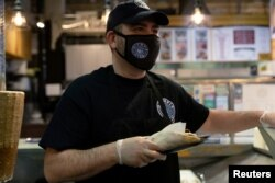 Athens Voulgaridis, owner of Olympia Gyro, serves customers at Reading Terminal Market that has seen reduced foot traffic due to the coronavirus disease (COVID-19) outbreak in Philadelphia, Pennsylvania, U.S., February 20, 2021. (REUTERS/Hannah Beier)