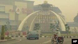 Seorang warga mengenakan masker untuk menutupi wajahnya saat mengendarai sepeda motornya melintasi wilayah Muar, Johor, Malaysia yang diselimuti polusi asap tebal, Sabtu (22/6). Pemerintah Malaysia menyatakan keadaan darurat di dua wilayah bagian selatan Johor akibat tingginya tingkat polusi di wilayah ini, Minggu (23/6).