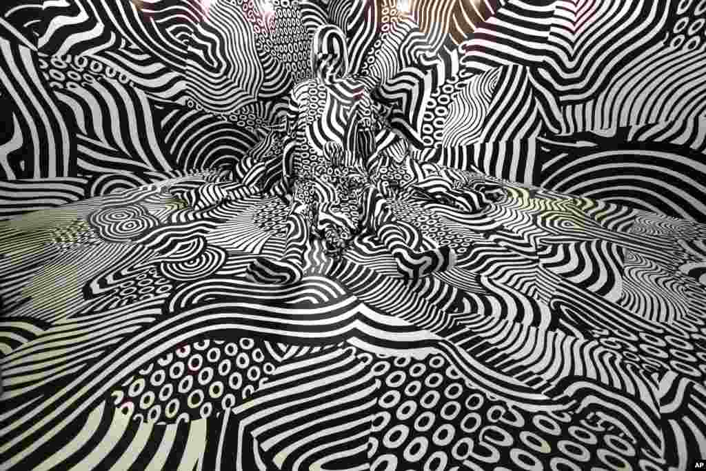 "A Model poses in an art installation ""Narcissism : Dazzle room"" by artist Shigeki Matsuyama at fashion and design exhibition in Tokyo, Japan."