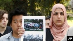 FILE - Ian Lee (l) and Fatima Sbeih (r) two of the students pepper-sprayed at the University of California, Davis, November 2011, are seen behind photos of the incident displayed during a news conference where the terms of a lawsuit settlement was discussed at UC Davis in Davis, Calif., Sept. 26, 2012.