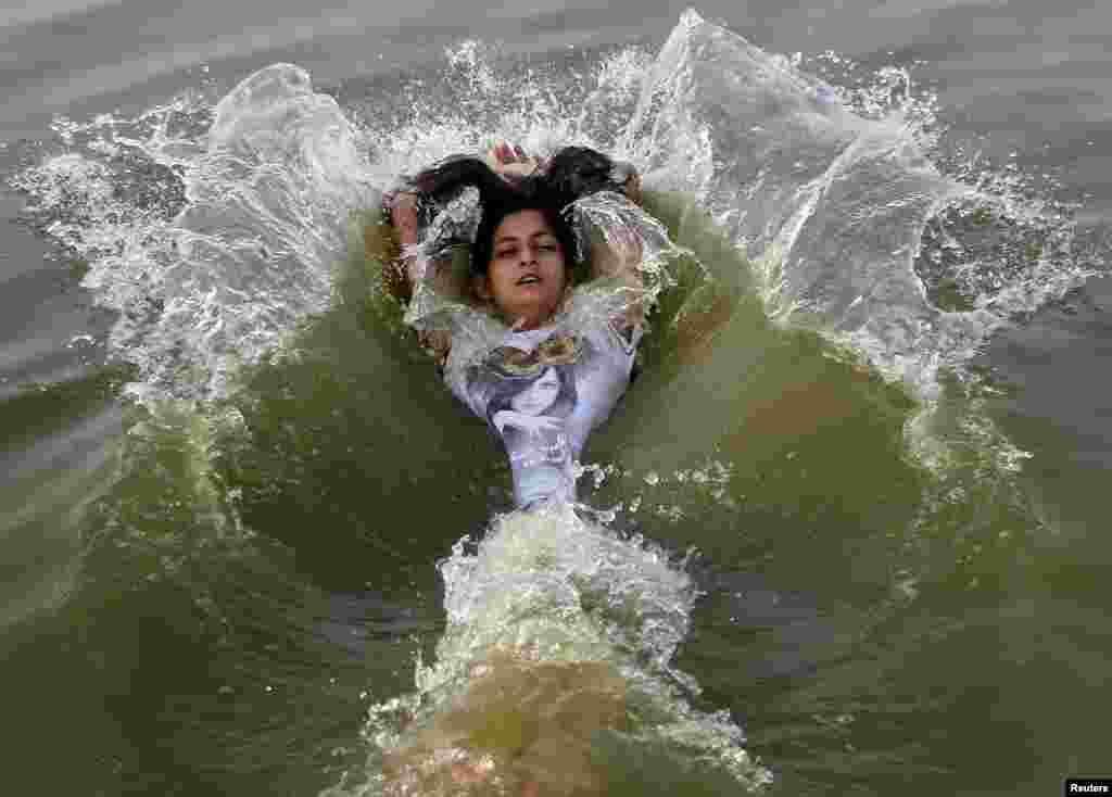 Seorang anak perempuan bermain di air di Sungai Gangga di hari yang panas di Allahabad, India.