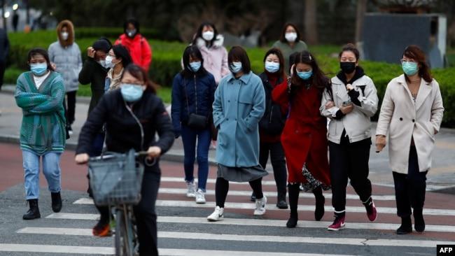 北京開始復工後,上班高峰期間的街頭行人。 (2020年3月26日)