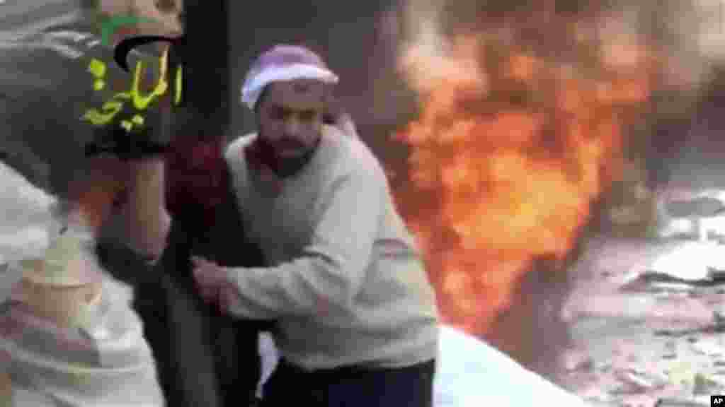 This citizen journalism image taken from video provided by Shaam News Network, which has been authenticated based on its contents and other AP reporting, shows a wounded man being pulled from the site of a Syrian government airstrike on a gas station in t