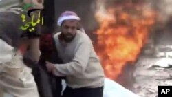 This image provided by Shaam News Network, which has been authenticated, shows a wounded man being pulled from the site of a Syrian government airstrike on a gas station in the eastern Damascus suburb of Mleiha, Syria, Jan. 2, 2013.