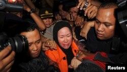 Gubernur Banten Ratu Atut Chosiyah (tengah), memakai rompi oranye KPK, saat ditangkap KPK di Jakarta, 10 Desember 2013.