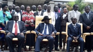 South Sudan's President Salva Kiir, center, laughs with First Vice President Riek Machar, left, and Vice President James Wani Igga, right, while cabinet members stand behind them, after the first meeting of a new transitional government of national unity.