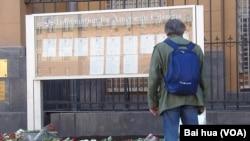 今年4月波士顿马拉松爆炸事件后,俄罗斯民众向美国表达慰问支持。一位行人当时在观看美国大使馆前莫斯科市民献的花。(美国之音白桦拍摄)