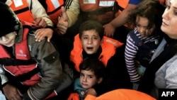 Des réfugiés syriens après le naufrage de leur embarcation près de l'île grecque de Lesbos, 30 oct. 2015. (AFP/ARIS MESSINIS)