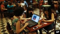 三名越南女孩在河内一家咖啡馆利用便携电脑和智能手机上网
