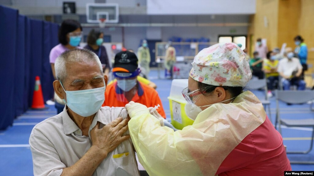 FILE PHOTO: A medical worker administers a dose of the AstraZeneca vaccine to a man during a vaccination session for elderly people over 75 years old, at a stadium in New Taipei City, Taiwan June 25, 2021.