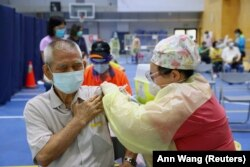 FILE - A medical worker administers a dose of the AstraZeneca vaccine to a man during a vaccination session for elderly people over 75 years old, at a stadium in New Taipei City, Taiwan June 25, 2021.