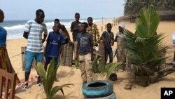 Au lendemainde l'attentat terroriste à Grand-Bassam, quelques curieux reviennent sur l'une des plages où a eu lieu l'attaque djihadiste. (AP Photo/Christin Roby)