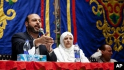 The Brotherhood's Freedom and Justice Party candidate Amr Zaki, left, is speaking to Cairo residents, November 26, 2011.