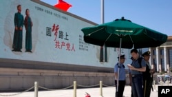 在北京天安门广场一个巨大的电子显示屏上的宣传口号:圆梦路上的共产党人。(2014年5月28日)