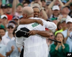 Tiger Woods reacts with his caddie Joe LaCava as he wins the Masters golf tournament, April 14, 2019, in Augusta, Ga.