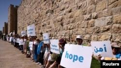 Sejumlah aktivis perempuan Israel, baik yang berasal dari etnis Yahudi maupun Arab, melakukan aksi unjuk rasa menyerukan perdamaian di luar tembok Kota Tua Yerusalem hari Rabu (19/5) (Foto: Reuters/Ronen Zvulun)