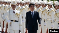 Japan's Prime Minister Shinzo Abe reviews the honour guard before a meeting with Japan Self-Defense Force's senior members at the Defense Ministry in Tokyo, Sept. 12, 2013.