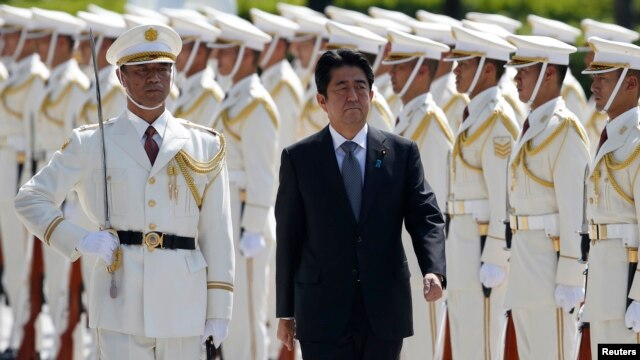 Japan's Prime Minister Shinzo Abe reviews the honor guard before a meeting with Japan Self-Defense Force's senior members at the Defense Ministry in Tokyo, Sept. 12, 2013.