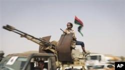 ກໍາລັງເສີມຂອງຝ່າຍກະບົດ ທີ່ມາຈາກນະຄອນຫລວງຕຣີໂປລີ ຂັບລົດຜ່ານດ່ານກວດແຫ່ງນຶ່ງລະຫວ່າງເມືອງ Tarhouna ກັບ Bani Walid, ໄປຍັງແນວໜ້າທີ່ເມືອງ Bani Walid, ວັນຈັນ ທີ 5 ກັນຍາ 2011.