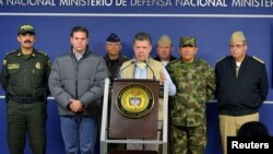 FILE - Colombia's President Juan Manuel Santos, center, speaks during a news conference in Bogota, Nov. 16, 2014.