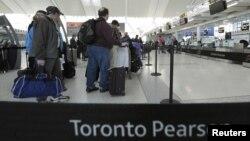Para penumpang antri untuk check-in di loket penerbangan Air Canada di bandara Pearson International, Toronto (Foto: dok). Lebih dari 200 penerbangan hari Natal di bandara ini telah dibatalkan akibat ancaman badai salju yang diramalkan akan melanda pantai Timur Amerika.