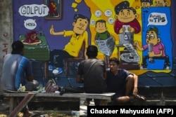 Orang-orang duduk di depan mural kampanye pemilihan umum Indonesia menjelang pemilihan bulan depan di Banda Aceh, Aceh pada 17 Maret 2019. (Foto: AFP/Chaideer Mahyuddin)