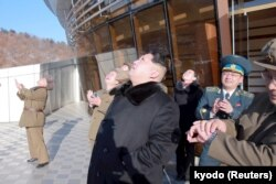 North Korean leader Kim Jong Un, center, watches a long range rocket launch into the air in North Korea, in this photo released by Kyodo, Feb. 7, 2016.