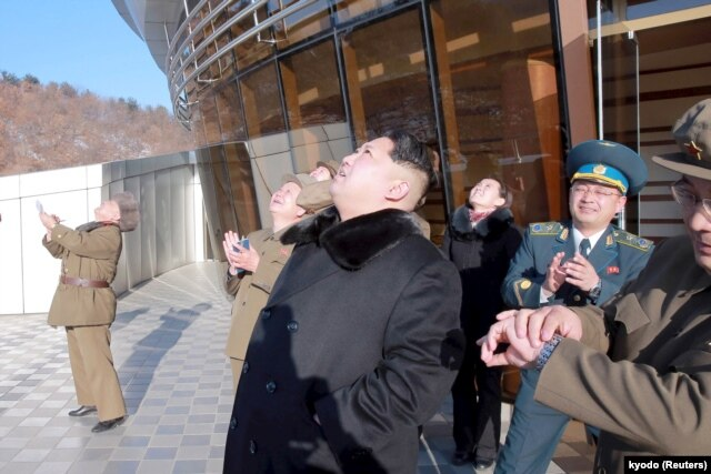 FILE - North Korean leader Kim Jong Un, center, watches a long range rocket launch into the air in North Korea, in this photo released by Kyodo, Feb. 7, 2016.