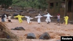 People wearing protective suits hold hands as they cross a river after a mudslide in the mountain town of Regent, Sierra Leone, Aug. 15, 2017, in this still image taken from a video.